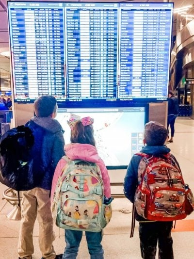 three kids with carry-ons in airport