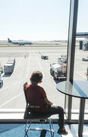 traveling with kids and child looking at plane from airport window