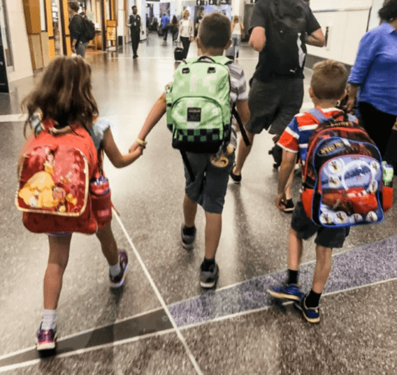 kids walking in the airport with backpack carry-ons