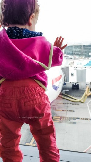 Young child looking out window at plane traveling with kids
