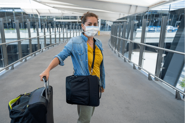 woman in airport with suitcase and mask - travel-in2020