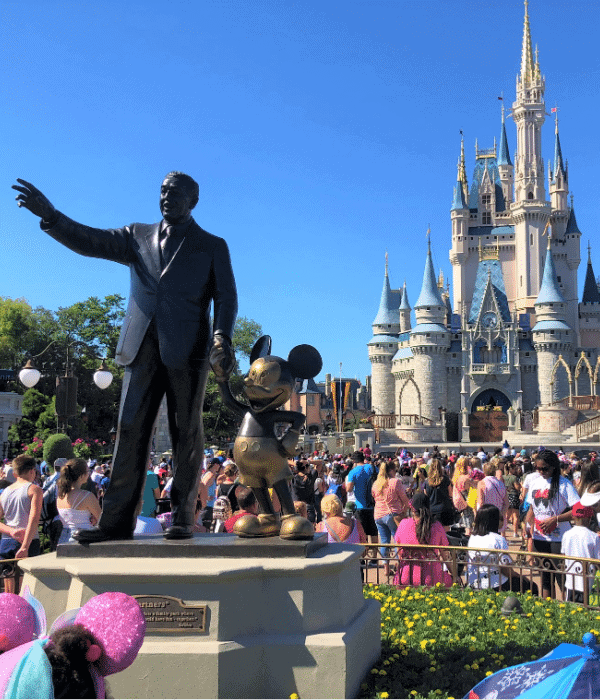 disney castle with statue of walt disney