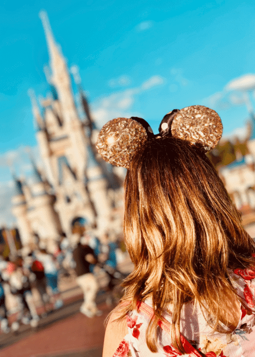 best things to do at disney world with teens and tweens: girl with gold mickey ears in front of Cinderella castle at walt disney world