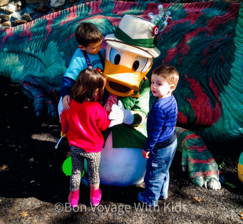 disney world with a toddler three kids hugging donald duck