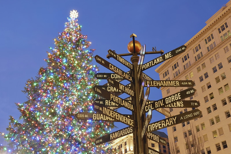 Christmas tree in portland with signs to other places holidays-around-the-world-for-kids