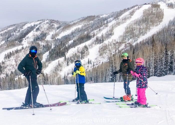 ski-trip-packing-list-family-posing-on-mountain