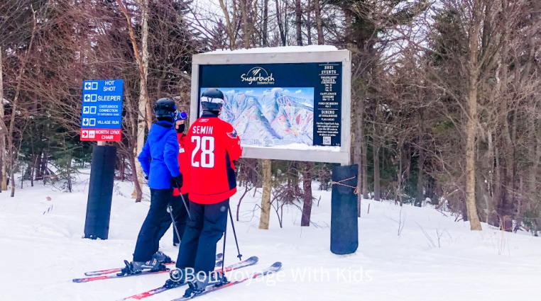 best-ski-resorts-in-vermont-people-looking-at-sugarbush-sign