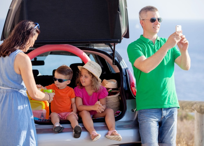 tips for road trips family inside car dad taking photo