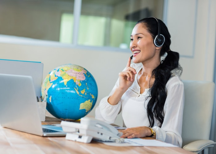 Why use a travel agent woman on phone in front of globe