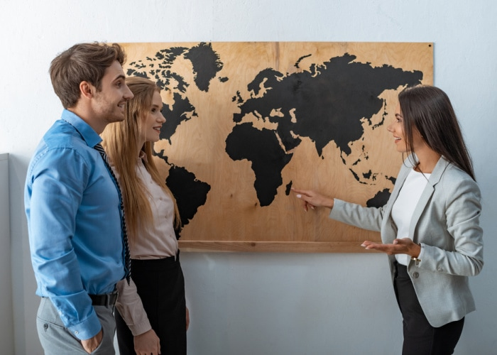 Why use a travel agent woman in front of map talking to clients