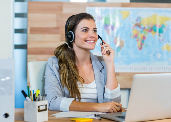 why use a travel agent travel agent on phone in front of computer and map