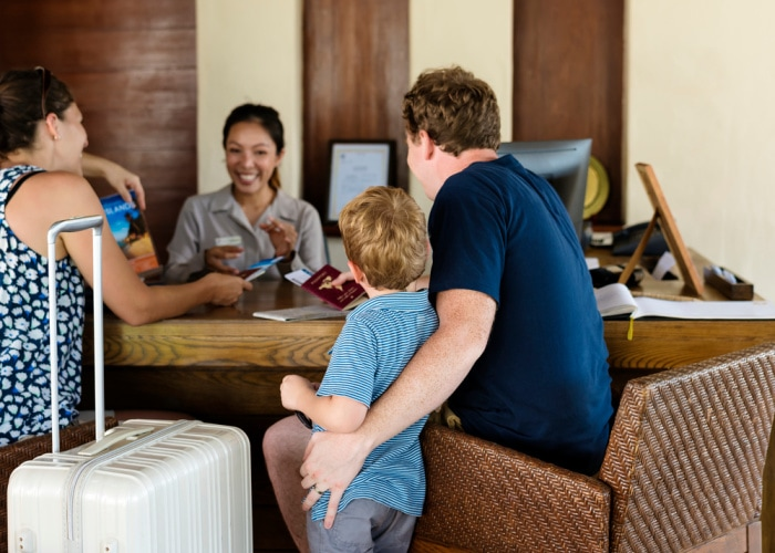 Why use a travel agent family talking to agent with a suitcase