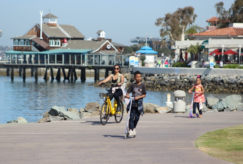 things-to-do-in-san-diego-with-kids-woman and kids riding scooter over san diego bay