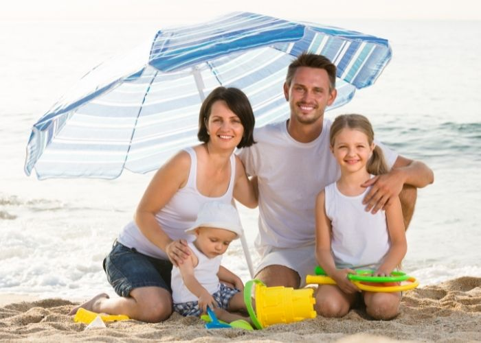 family posing on the beach - beach packing list family