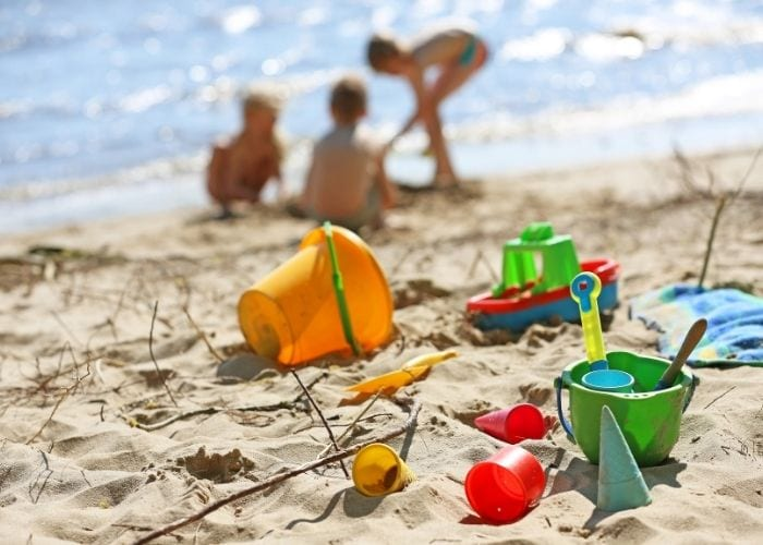 kids playing in the sand for beach packing list family