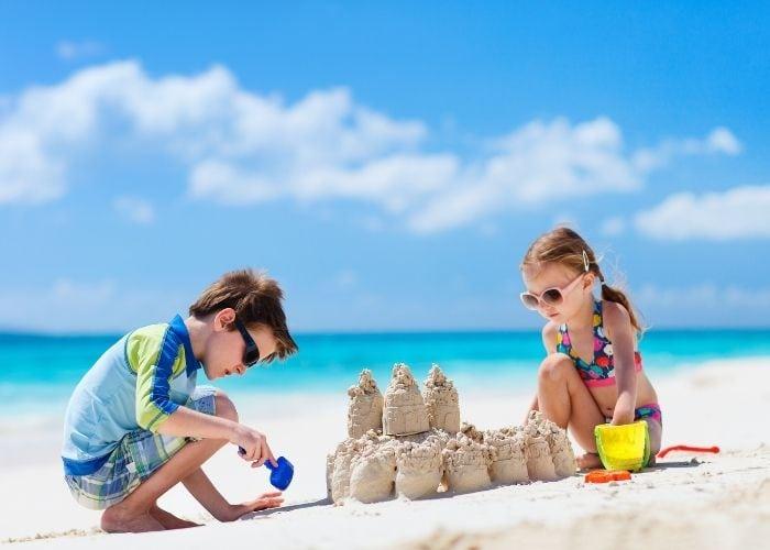 kids making sand castles for beach packing list family