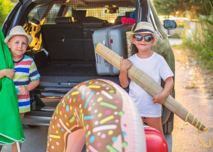 kids standing by car with beach essentials for beach packing list family