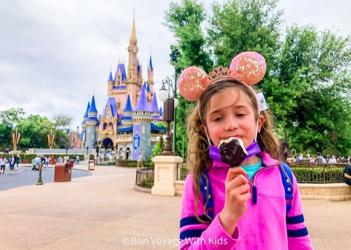 girl eating mickey bar in front of castle in Magic Kingdom